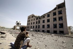 A Houthi militant sits amidst debris from the Yemeni Football Association building, which was damaged in a Saudi-led air strike, in Sanaa May 31, 2015. REUTERS/Mohamed al-Sayaghi